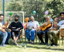 Bewoners maken muziek tijdens een open azc dag.